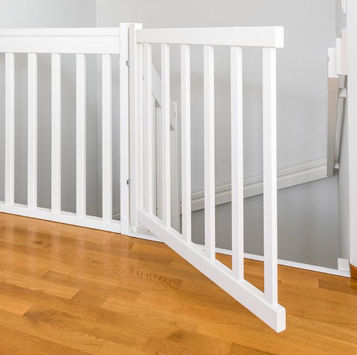 Valkoinen puinen lapsiportti yläkerrassa.