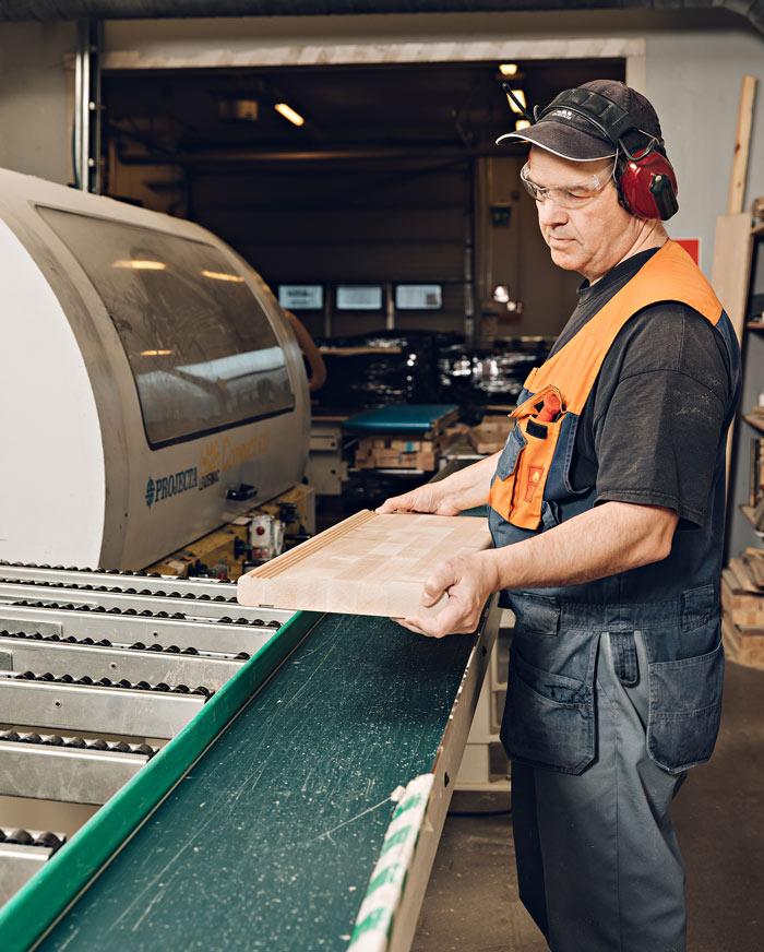 Puuseppä tarkastelee portaiden osia tehtaalla.