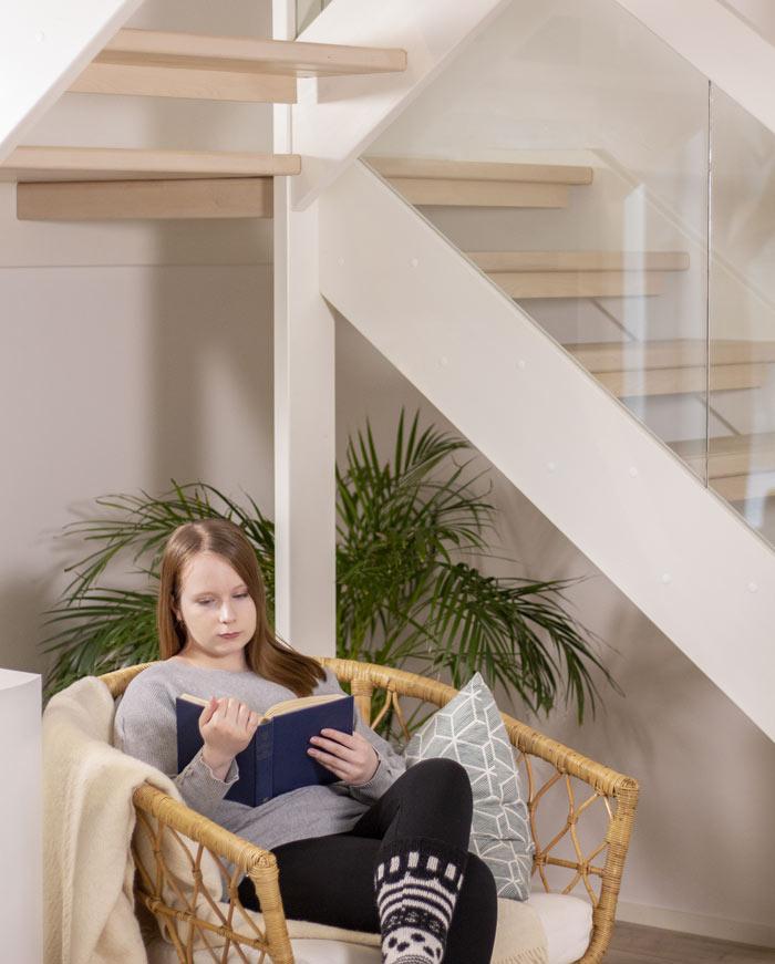 Tyttö lukee kirjaa portaiden juurella.