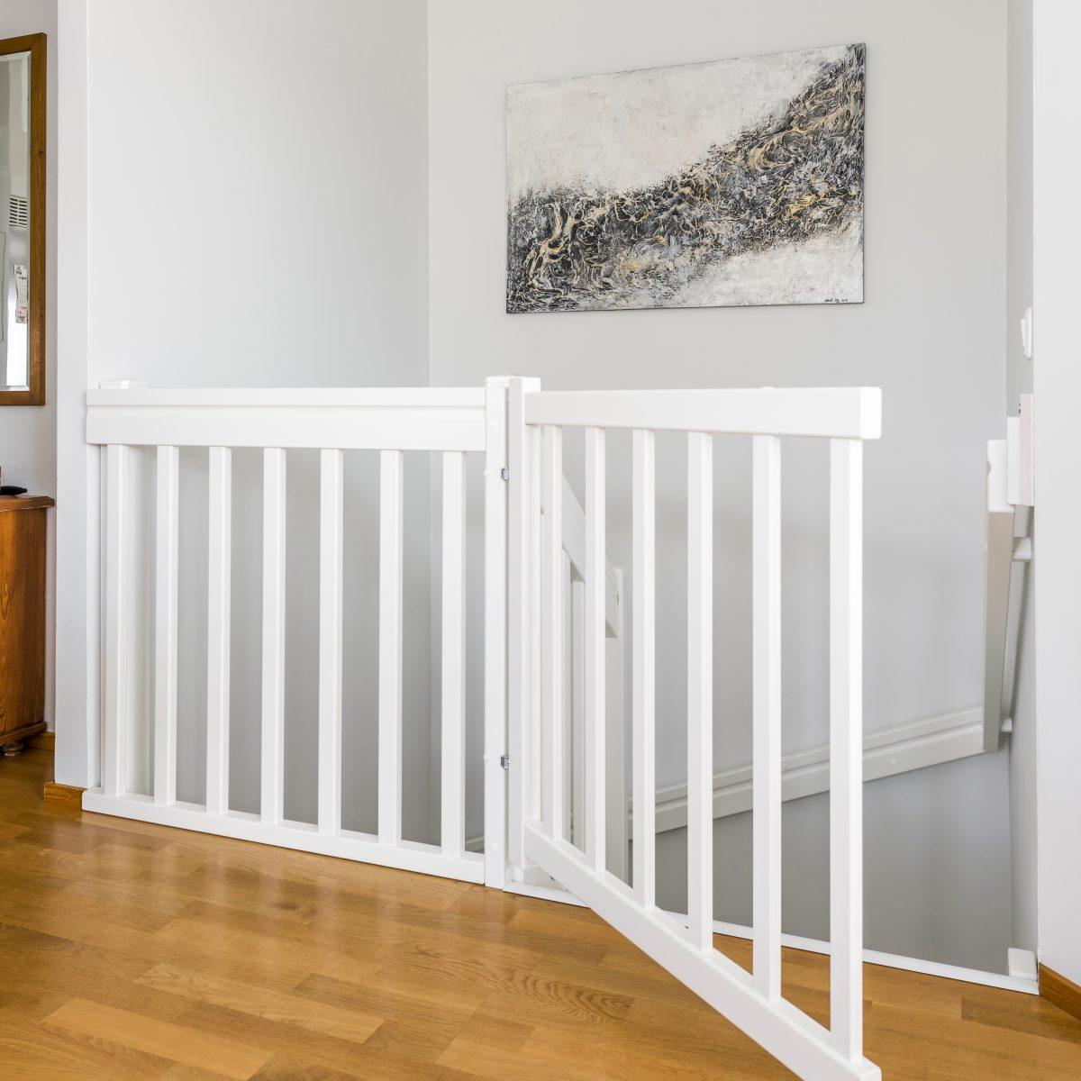 Kuva valkoisesta puukaiteesta talon yläkerrasta portaikon päästä
